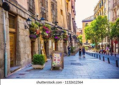 MADRID, SPAIN - July 2018: Traditional Madrid street and houses decorated with flowers, cafes and restaurants of Madrid, Spain