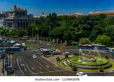 Madrid, Spain - July 21 2017: Ciberles Fountain with Spanish flags.Public buses and cars traffic around Plaza de Cibeles viewed from Cybele Palace at the Spanish capital.