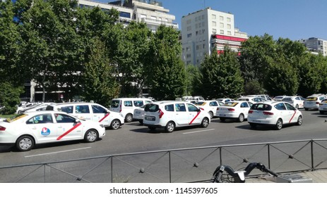 Madrid, Spain - July 30, 2018 - Taxi vehicles stopped along Castellana avenue due to general Taxi strike in Madrid against Uber and Cabify services