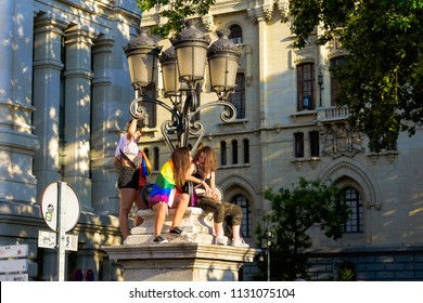 MADRID, SPAIN - JULY 7, 2018: Pride parade. A group of youngs up on a streetlight in the Gay pride parade
