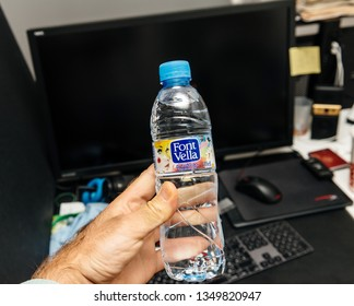 Madrid, Spain - Jun 11, 2018: Man hand holding pet plastic bottle of Font Vella water bootle produced by Danone against office background