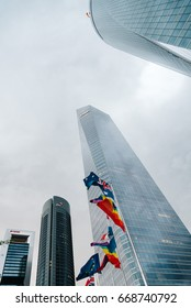 Madrid, Spain - June 25, 2017: Low angle view of Cuatro Torres Business Area, CTBA, Four Towers Business Area,  a business district. Flags waving against buildings during Madrid World Pride 2017