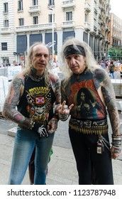 MADRID, SPAIN - JUNE 29, 2018: Portrait of two heavy metal men making heavy rock sign with the hand in gran via street in Madrid. They are known as los heavies de la gran via