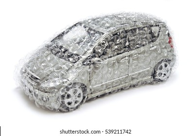 Madrid, Spain - June two thousand and ten: isolated on white silver mercedes benz A class minivan toy car made in two thousand and nine wrapped in transparent bubbles wrap.