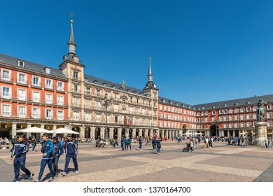 Madrid / Spain - March 15, 2019: Four young men and other people walking around the Plaza Mayor in Madrid, Spain, the main town square of the city.