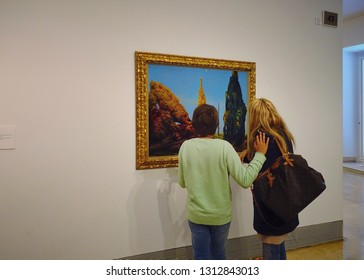 """MADRID, SPAIN - MARCH 26, 2018: Visitors in the museum Thyssen-Bornemisza  look at the picture """"Solitary and Conjugal Trees"""", 1940 by Max Ernst"""