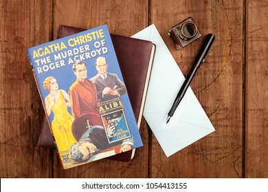 Madrid, Spain, March, 5, 2018. The Murder of Roger Ackroyd, a detective novel by Agatha Christie, with a leather journal, a blue envelope, and an ink well and pen, on a dark background with copy space