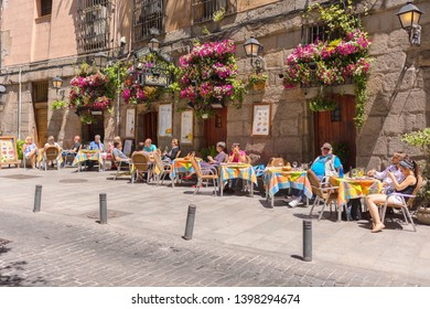 Madrid, Spain- May 10, 2019 – Old cozy street in Madrid with small restaurant with outdoor tables in city center near Plaza de San Miguel full of tourists eating best tapas and local traditional food