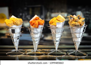 Madrid, Spain - May, 10, 2019 - Sea food in cones at counter in smal street shop in Spain – snack with mixed takeaway grilled fish and fried seafood – delicious roasted octopus, anchovies and calamari