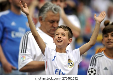 MADRID, SPAIN - May 13th, 2015 :  young kid fan of REAL MADRID cheering the team excited during Europe Champions League match VS JUVENTUS at Santiago Bernabeu Stadium