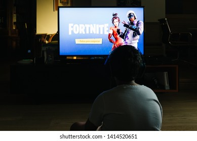 Madrid, Spain - May 29, 2019: Teenager playing Fortnite video game withn Playstation on TV. Fortnite is an online multiplayer video game developed by Epic Games