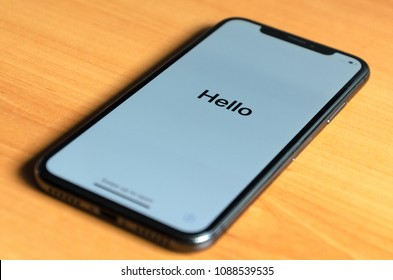 MADRID, SPAIN - MAY 9, 2018: New Apple iPhone X greeting with a hello over a wood table. Iphone X is the most new expensive Apple smartphone