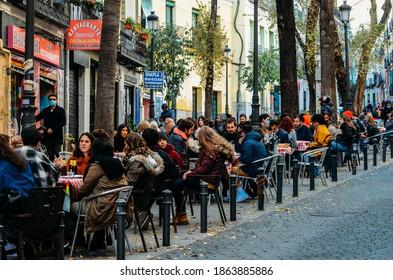 Madrid, Spain - Nov 29, 2020: People sitting on a terrace in the neighborhood of Lavapies in Madrid