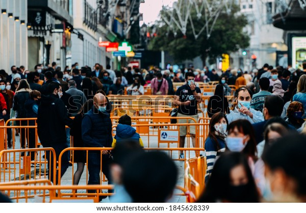 Madrid, Spain - November 1st, 2020: Crowded pedestrian street in Madrid, Spain. People wear obligatory face covering during the Covid-19 pandemic. Captured at 300mm. Bokeh selective focus