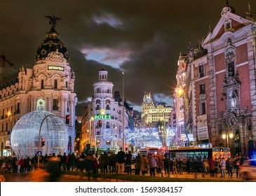 Madrid, Spain - November 23, 2019. Gran Via street at nightfall illuminated by christmas lights and a shinny christmas ball. View from Alcala street.