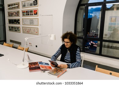 Madrid, Spain - November 3, 2017:  Woman reading at coworking in Centro Cibeles in the new City Hall of Madrid. Located in the Cybele Palace it is a trendy cultural center for the city