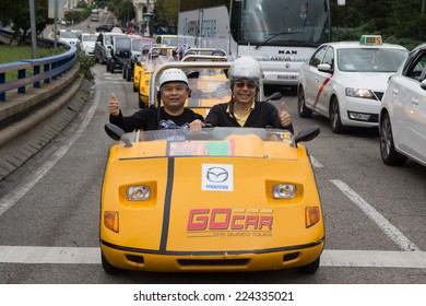 MADRID, SPAIN - OCTOBER 11, 2014: Tourist in a GoCar in the streets of Madrid. GoCar is a two-seater, 3 wheeled vehicle for the purpose of being rented to tourists as a different way to see a city.
