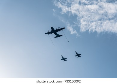 Madrid, Spain - October 12, 2017: Hercules KC-130 tanker aircraft refuelling in flight two jet fighters in Spanish National Day Parade.