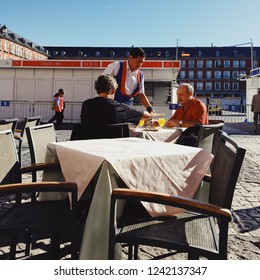 Madrid, Spain - October 23, 2017: A waiter is serving breakfast to two gentlemen sitting on an outdoor table at the Plaza Mayor.