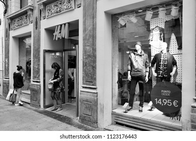 MADRID, SPAIN - OCTOBER 24, 2012: People shop at H&M store in Madrid. H&M is an international fashion retail corp known for its fast fashion approach. Founded in 1947, it employs 87,000 people (2011).