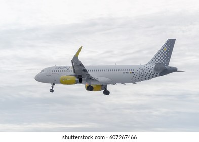 MADRID, SPAIN - OCTOBER 24th 2015: Plane Airbus A320, of Vueling airline, is landing on Madrid - Barajas, Adolfo Suarez airport, on October 24th 2015. Moment when it's getting dark. Cloudy sky. Autumn