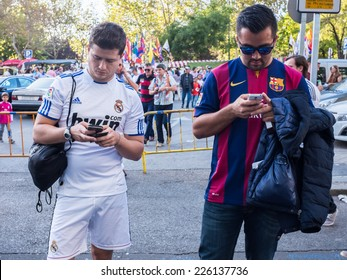 MADRID, SPAIN - OCTOBER 25, 2014: A couple of friends supporting Real Madrid and Barcelona watching their Smartphones at Santiago Bernabeu Stadium Gates before the Real Madrid-Barcelona match.