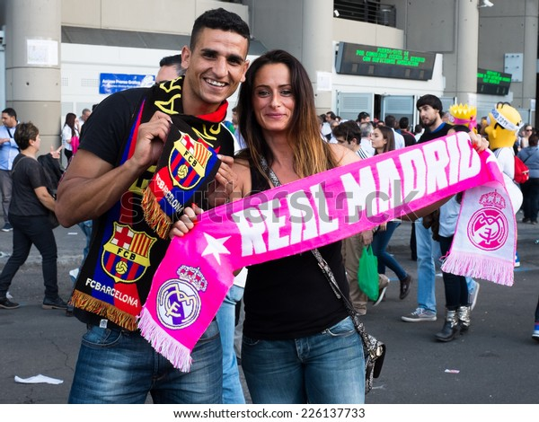 MADRID, SPAIN - OCTOBER 25, 2014: A young couple support Real Madrid and Barcelona FC soccer teams at the Real Madrid-Barcelona match.