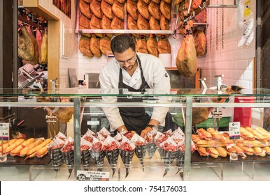 Madrid, Spain - October 7, 2017: Man at a Food Stand Selling Iberico Ham in San Miguel Market