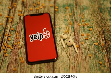 Madrid, Spain - September 10, 2019; Yelp Apple Iphone XS Application Screen on a Rustic Wooden Table with Earpiece and Corn Seed