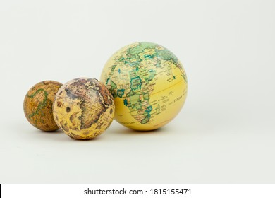 Madrid, SPAIN - September 10, 2020:Vertical shot of three earth globe vintage maps isolated on a white background with negative space and soft shadow. Travelling and cartography concepts.