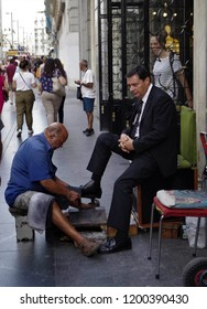 Madrid, Spain - September 24 2018: a poor shoeshiner on the street clean the shoes of an elegant white man, focusing on his job and nothing else