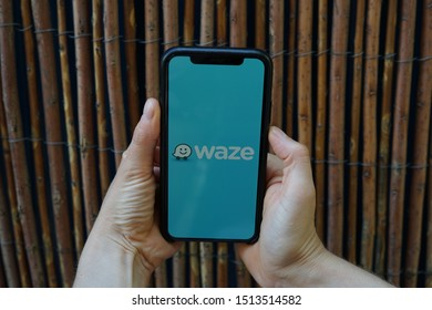 Madrid, Spain - September 25, 2019; Waze Iphone XS Application Screen Held by a Girl with Wooden Wall Background