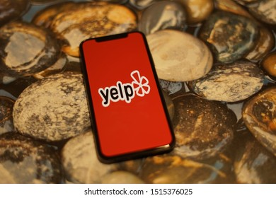 Madrid, Spain - September 27, 2019; Yelp Apple Iphone XS Application Screen on a Wet River Rocks Background