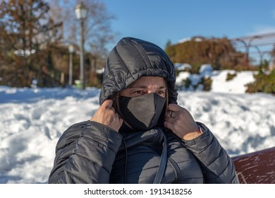 Madrid, Spain.January 16, 2021.Middle-aged woman with protective face mask sitting on a bench in a snowy public park covers her head with the hood of her coat.