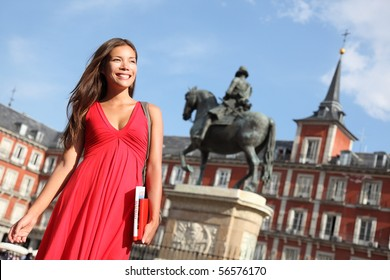 Madrid. Woman tourist walking on Plaza Mayor Madrid, Spain. Beautiful woman in red dress. Tourist attraction, statue of Felipe III in the background.