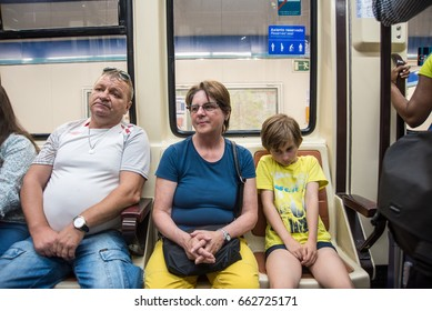 Madrid,Spain- June 9,2017: A man sits with his legs spread wide next to a woman in the Madrid Subway