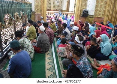 Madura, Indonesia - January 1, 2018: A group of moslems pray in front of the tomb preacher inside the mosque in Bangkalan, Madura, East Java, Indonesia