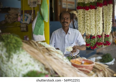 MADURAI, INDIA - AUG 12: Unidentified man sell flowers in flower market on August 12, 2012 in Madurai, India. In India poor grassroots often sell flowers to earn a small cash income.