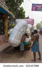 Madurai, India - October 22, 2013: Huge cotton bales are unloaded from a small truck in a downtown street early in the morning. One man carries a huge bale on his back, while another man looks on.