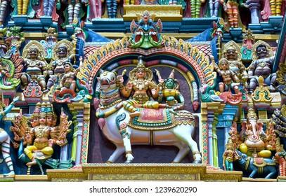 Madurai Tamil Nadu India August 24 2009 Stucco figers of shiva and parvati  and guards on the gopuram of sri meenakshi temple