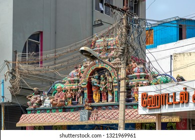 MADURAI, TAMIL NADU, INDIA - OCTOBER 27, 2018: A utility pole supporting a mass of wiring, some of it haphazard, positioned outside and obscuring a temple in the Indian city of Madurai.