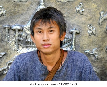 MAE CHAEM, CHIANG MAI / THAILAND - NOV 21, 2015: Young Thai repoussé master artist poses for the camera in front of his religious artwork at Wat Jiang Temple, on Nov 21, 2015.