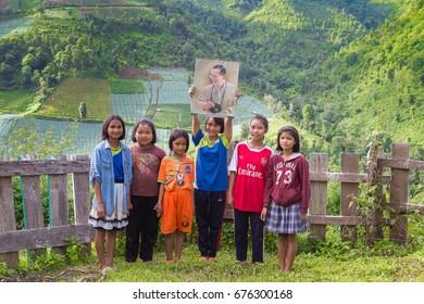 MAE HONG SON PROVINCE, THAILAND, 9 JULY 2017: A group of Karen children is holding beloved portrait of King Bhumibol Adulyadej.