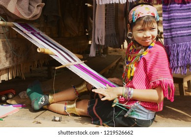 Mae Hong Son, Thailand - November 17, 2008: Unidentified girl of the Lahwi Padaung hill tribe wearing traditional dress weaves outside of a house in Kayan village in Mae Hong Son, Thailand.