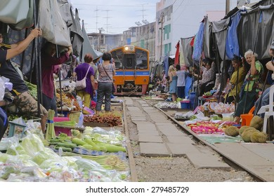 MAE KONG MARKET SUMUTHSONGKRAM,THAILAND-JULY 30 2014: The market market where they have to prepare to fold down umbrella or awning to let the trains pass through