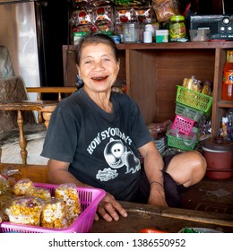 Mae Salong / Chiang Rai Province, Thailand-January 22, 2017: Portrait of woman smiling showing her red teeth coloured by areca nut . She sits in her grocery, among caramelized popped-corn bags