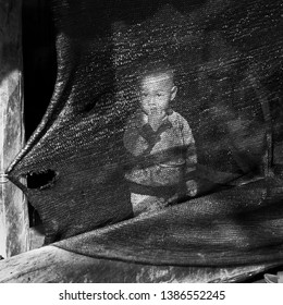 Mae Salong / Chiang Rai Province, Thailand-January 22, 2017: Black and white picture with a little boy sucking on his fingers behind a torn tarpaulin  produced with a transparent weft .