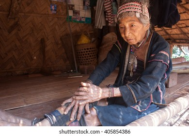 MAE SALONG,  CHIANG RAI, THAILAND - MAY 2, 2005 :  North of Thailand during summer. An old woman from the Akha ethnic group rests in the shadow of her house, the temperature can reach 40 degrees .