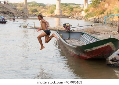 MAE SOT, TAK, THAILAND - APRIL 19, 2016 : Unidentified boy is jumping into the river at the natural harbor, Rim Moei, Mae Sot, Tak, Thailand.