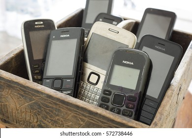 MAE SOT, TAK, THAILAND - JANUARY 06, 2017 : Keypad cell-phone brand Nokia placed on the old wooden basketry at Mae Sot, Tak, Thailand. The keypad Nokia cell-phone was a very popular in Thailand.